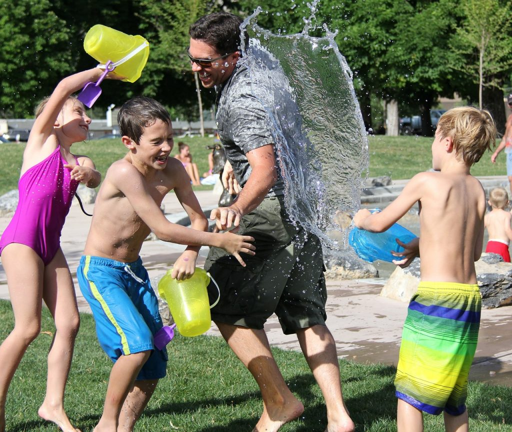 Children playing throwing water buckets on their heads.
